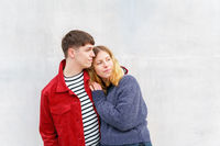young affectionate couple standing in front of concrete wall