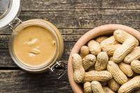 Peanut butter in jar and peanuts.
