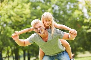 Mann tobt mit Tochter auf dem Rücken
