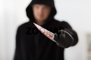 close up of criminal with blood on knife