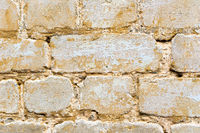 Textured background of a multi-colored brick painted in yellow. A sizzling yellow paint on an old broken brick. Grunge style