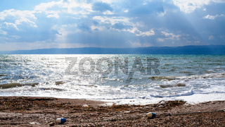 dirty beach of Dead Sea in cloudy winter day