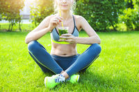 Woman drinking after fitness running workout on summer day.