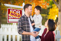 Mixed Race Chinese and Caucasian Parents and Child In Front of Fence and Sold For Sale Real Estate Sign.