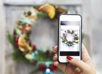 Woman makin photo of cristmas wreath