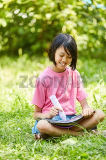 Asiatisches Mädchen malt ein Bild mit Kreide