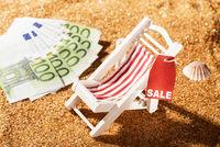 Liegestuhl mit Rabatt Etikett und Geldscheinen