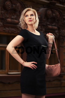 Happy young fashion blond woman in black dress walking in city street