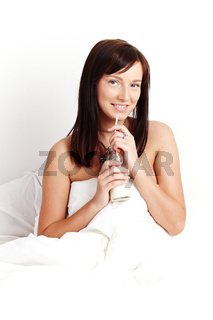 Young beautiful woman drinking milk sitting on white bed