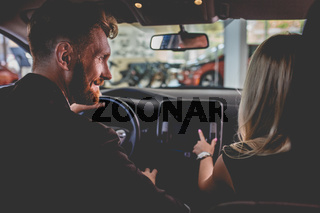 Man and woman sitting on front seats of new car.