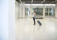 Pregnant woman with suitcase at airport or station
