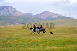 Pair riding the horses with a kid, Kyrgyzstan