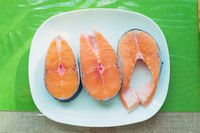 three fresh salmon steaks on a white plate standing on a green table.