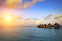 houses over the transparent quiet sea water  on a sunset. Maldives