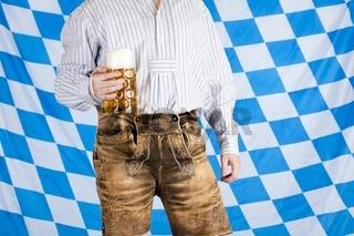 Bayerischer Mann in Lederhose hält Oktoberfest Bier Krug