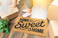 Woman in Pink Shoes and Sweats Unpacking Near Home Sweet Home Welcome Mat, Moving Boxes and Plant