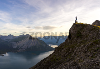 Young man celebrates reaching the peak of a mountain