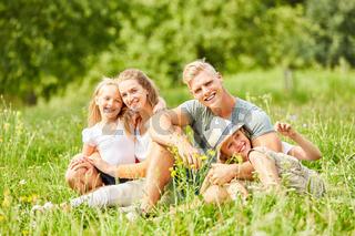 Familie sitzt entspannt in der grünen Natur