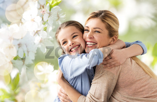 happy mother hugging daughter over cherry blossom
