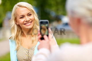 senior mother photographing daughter by smartphone