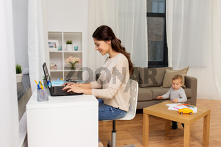 happy mother with baby and laptop working at home
