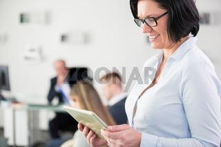 Ältere Geschäftsfrau schaut auf Tablet PC