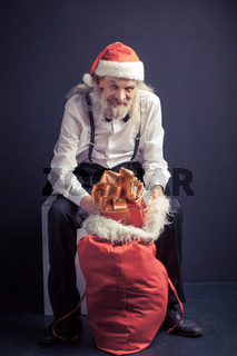 Old man in Santa hat sitting on chair with gift bag.