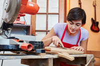 Frau als Azubi lernt Gitarrenbauer
