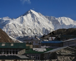 Lodges in Gokyo and snow covered mount Cho Oyu. Spring scene in Solu Khumbu, Nepal.