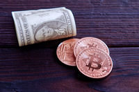 Dollar banknotes and Bitcoins on a dark wooden table