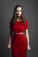 Seductive woman in red dress over gray background