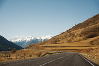 View of the autumn road leading to the mountains to the snow-capped peaks of the Caucasus. The concept of traveling to the mountains by car