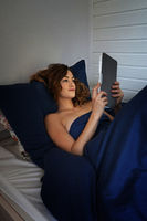 young woman using e-book reader or tablet computer in bed