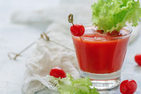 Tomato juice with ice cubes and a leaf of lettuce.