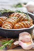 Potatoes in their skins baked with rosemary.