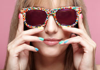 Young blonde smiling  woman with fun candy glasses and varicoloured finger nails manicure