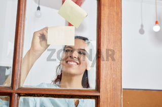 Frau notiert kreative Ideen auf Zetteln