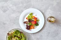 Two plates with fresh salad on a gray background