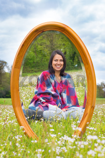 Mirror in spring meadow with sitting pretty woman