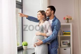 man showing something out window to pregnant wife