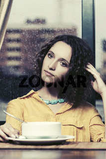 Sad young fashion woman eating a soup at restaurant