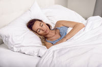 Woman sleeping in bed under quilt