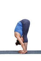 Woman doing yoga asana Uttanasana - standing forward bend