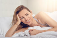Happy friendly woman relaxing in bed