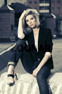 Sad beautiful fashion woman sitting on the city sidewalk