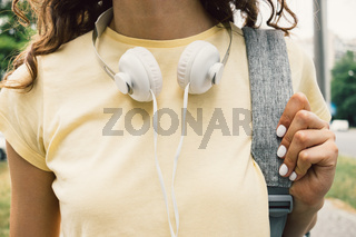 Close-up of a girl in a yellow T-shirt and headphones in the city