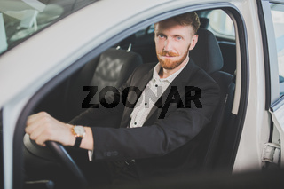Young handsome man bying car, inspecting interior of the vehicle.