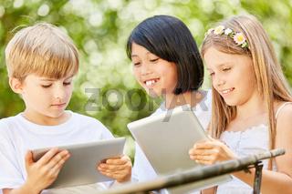 Drei Kinder mit Tablet PC lernen zusammen