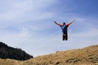 männlicher Wanderer macht Freudensprung