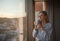 young woman enjoying evening coffee by the window